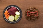 vrchní pohled na suché krmivo pro domácí zvířata s kostí v blízkosti syrové zeleniny a masa v misce na dřevěném stole