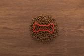 vrchní pohled na suché krmivo pro domácí zvířata s kostí na dřevěném stole