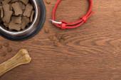 vrchní pohled na suché krmivo pro domácí mazlíčky ve stříbrné misce u kosti, obojek na dřevěném stole