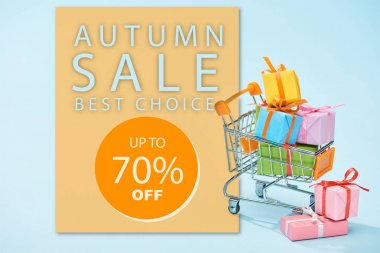 Festive wrapped presents in shopping cart on blue background with autumn sale, up to 70 percent off illustration stock vector