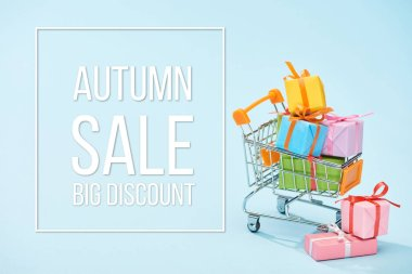 Festive wrapped presents in shopping cart on blue background with autumn sale big discount illustration stock vector
