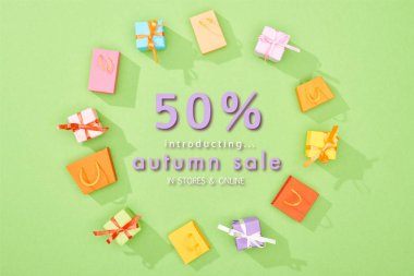 Round frame of decorative gift boxes and shopping bags on green background with 50 percent off autumn sale illustration stock vector