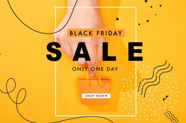 Cropped view of hand holding small shopping bag on bright orange background with black Friday sale illustration stock vector
