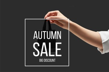 Cropped view of woman holding small black shopping bag in hand isolated on black with autumn sale illustration stock vector