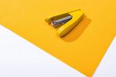 vysoký úhel pohledu na žlutou sešívačku na světlém papíru izolovaném na bílém