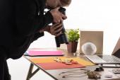 Fotograf fotografiert Kompositionen mit Flora und Zubehör für kommerzielle Fotoshootings mit Kamera und Laptop