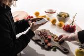 oříznutý pohled na dva fotografy, jak na dřevěném stole vyrábějí potravinovou kompozici pro komerční fotografii