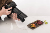 cropped view of female photographer making food composition for commercial photography and taking photo on digital camera on white