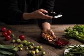 oříznutý pohled na fotografa, jak na dřevěném stole vytváří kompozici potravin pro komerční fotografii