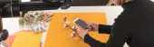 Ausgeschnittene Ansicht des Fotografen, der Komposition mit Baumwollblume und Accessoires auf Smartphone fotografiert, Panoramaaufnahme