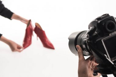 cropped view of commercial photographers making commercial photo shoot of female red heel shoes on white