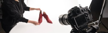 cropped view of commercial photographer making commercial photo shoot of female red heel shoes on white, panoramic shot