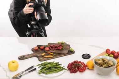 Cropped view of female photographer making food composition for commercial photography and taking photo on digital camera stock vector