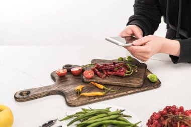 cropped view of professional photographer making food composition for commercial photography on smartphone