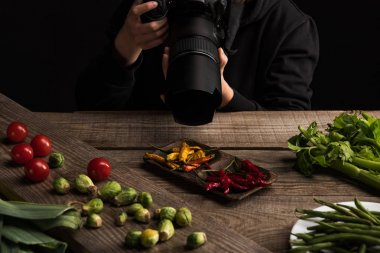 Cropped view of female photographer making food composition for commercial photography and taking photo on digital camera on wooden table stock vector