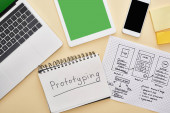horní pohled na miniaplikace v blízkosti šablony designu webových stránek a notebooku s prototypovým písmem na žlutém pozadí