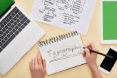 oříznutý pohled návrháře psaní typografie písmo v notebooku v blízkosti webové stránky design šablony a gadgets na žlutém pozadí