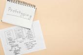 horní pohled na šablonu designu webových stránek a notebook s prototypovým písmem na béžovém pozadí