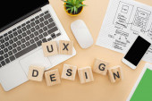 top view of gadgets near wooden blocks with ux design lettering, website design template and green plant on beige background