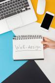 oříznutý pohled ženy držící notebook s webovým designem nápisy v blízkosti notebooku, smartphonu, počítačové myši na abstraktním geometrickém pozadí
