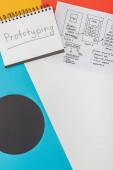 horní pohled na notebook s prototypovým písmem a šablonou designu webových stránek na abstraktním geometrickém pozadí