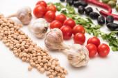 zblízka pohled na cizrnu, česnek, cherry rajčata, petržel, olivy na bílém pozadí