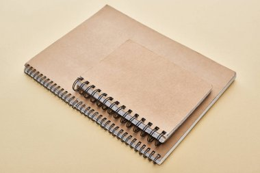 two paper blank notebooks on beige background