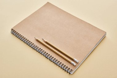 paper blank notebook with pencils on beige background