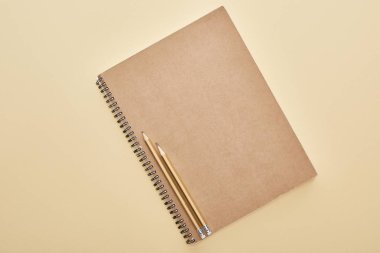 top view of  paper blank notebook with pencils on beige background