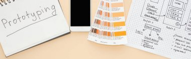 top view of smartphone near website design template, color palette and notebook with prototyping lettering on beige background, panoramic shot