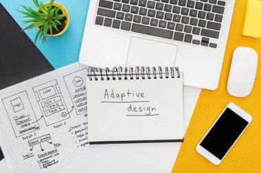 top view of website design template near notepad with adaptive design lettering, laptop, computer mouse, smartphone, plant on abstract geometric background