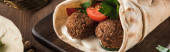close up view of falafel with vegetables and sauce on pita on wooden table, panoramic shot