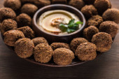 close up view of falafel balls with hummus on plate on wooden table