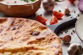 Fotografie Tradiční gruzínská imereti khachapuri se zeleninou a kořením na stole