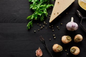 vrchní pohled na lahodné vařené escargots na černém dřevěném stole se složkami