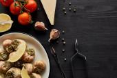 vrchní pohled na lahodné vařené escargots s plátky citronu na černém dřevěném stole se složkami