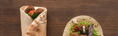 Top view of falafel with vegetables and sauce wrapped and unwrapped in pita on wooden table, panoramic shot stock vector
