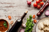 vrchní pohled na lahodné khinkali poblíž láhve vína, kharcho, zeleniny a koření na dřevěném stole