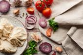 vrchní pohled na lahodné khinkali u zeleniny, koření a ubrousek na dřevěném stole