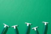 vrchní pohled na zelené jednorázové holicí strojky na zeleném pozadí