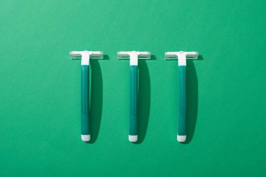 Flat lay with green disposable razors on green background stock vector