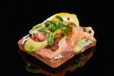 Close up of avocado near salmon on danish smorrebrod sandwich on black stock vector