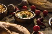 vynikající hummus, cizrna, pita, zelenina a koření na dřevěném rustikálním stole