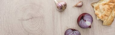 Top view of delicious fresh baked pita, garlic and red onion on beige wooden table, panoramic shot stock vector