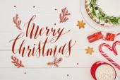 vrchní pohled na vánoční koláč s polevou na bílém dřevěném stole s candy canes, dárky a kakao s veselou vánoční ilustrací