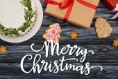 top view karácsonyi pite, cookie-k és ajándékdobozok sötét fa asztal boldog karácsonyi illusztráció