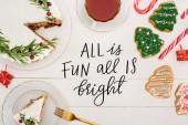 top view di torta di Natale con rosmarino, tazza di tè e biscotti albero di Natale sul tavolo di legno bianco con tutto è divertente tutto è illustrazione luminosa