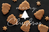 Fotografie top view of snowflake and Christmas tree cookies on black wooden table with Merry Christmas illustration