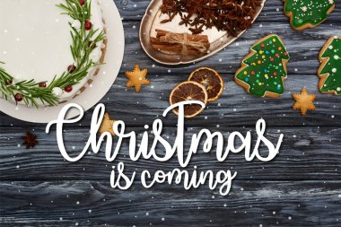 top view of christmas pie, spices and cookies on dark wooden table with Christmas is coming illustration