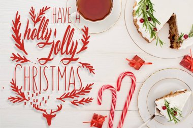 Top view of christmas pie on white wooden table with cup of tea, candy canes and little gifts with have a holly jolly Christmas lettering stock vector